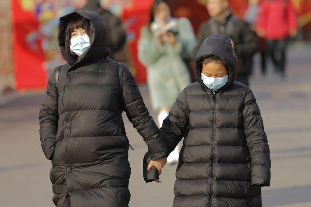 Védőmaszkos gyalogosok Pekingben 2020. január 21-én. A kínai fővárosban és a dél-kínai Sencsenben is felbukkant új, tüdőgyulladást okozó vírus kiindulópontjának számító közép-kínai Vuhanban jelentősen megugrott a fertőzöttek száma, a vírusfertőzés eddig legkevesebb négy ember halálát okozta. (Fotó: MTI/EPA/Vu Hong )