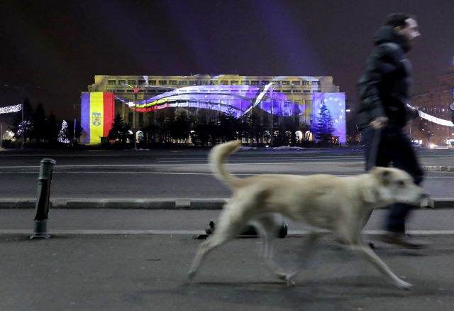A man accompanied with his dog pass by the Victoria Palace (the goverment headquarters, in the background) that is video-mapped with the projection of EU (R) and Romanian (L) flags, as well as the as the official logo of the Romanian Presidency at the Council of the European Union (C), in Bucharest, Romania, late 31 December 2018. Romania is preparing to take the Presidency of the Council of the European Union for six months, starting on 01 January 2019. EPA/ROBERT GHEMENT