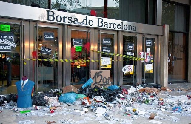 Ti vagytok a hibásak! - sugallja a sötétszürke felirat a Barcelonai Tőzsde bejáratán egy pár évvel ezelőtti, megszorítás-ellenes tüntetés után.