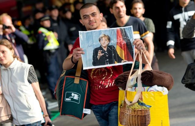 Magyarországról Ausztrián keresztül Németországba érkezett bevándorló Angela Merkel képét mutatja a müncheni főpályaudvaron. Kép forrása: MTI