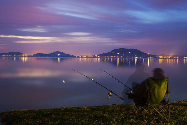 Egy férfi horgászik a balatonfenyvesi szabadstrandnál  MTI Fotó: Varga György