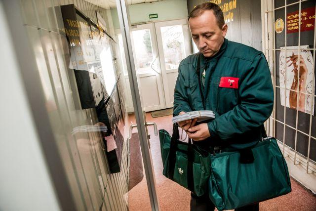 A Magyar Posta Zrt. munkatársa viszi a nyugdíjasoknak kézbesítendő Erzsébet-utalványokat tartalmazó borítékokat. (Kép forrása: MTI Fotó, Balogh Zoltán)