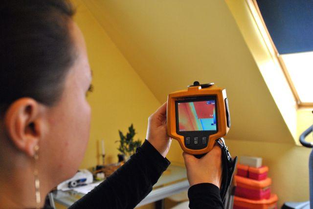 Szántó Beatrix, az Obex Kft. dolgozója egy eladásra váró lakásnál hőkamerával felületi hőeloszlást mér. (Kép forrása: MTI Fotó, Balaton József)