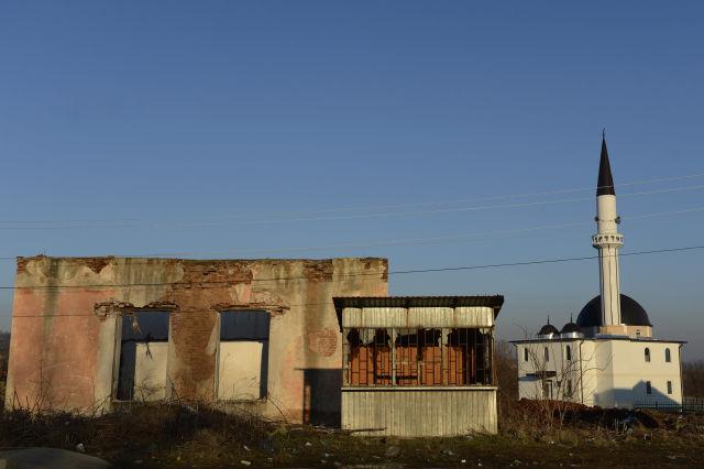 Elhagyott épület egy dzsámi és egy minaret mellett Podujeve városban, a koszovói-szerb határ közelében (Kép forrása: MTI Fotó, Kovács Tamás)