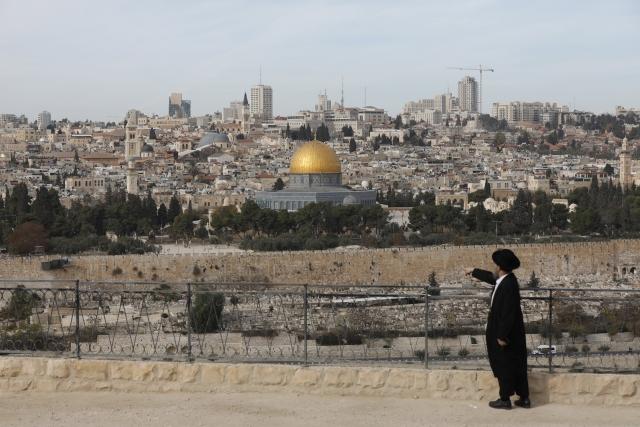 Ultraortodox zsidó férfi az Olajfák hegyén, a háttérben a jeruzsálemi óváros az al-Aksza-mecset kertjében álló Szikladóm (Omar-mecset) arany kupolájával 2017. december 5-én. Donald Trump amerikai elnök várhatóan december 6-án nyilatkozik arról az Egyesült Államok elismeri-e Jeruzsálemet Izrael fővárosaként. (MTI/EPA/Abir Szultan)