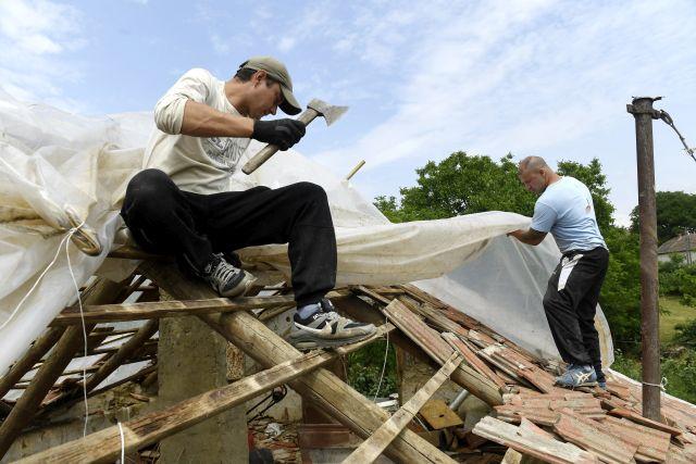 Villámsújtotta családi ház tetejének ideiglenes javításán dolgoznak önkéntesek a Jász-Nagykun-Szolnok megyei Csépán (MTI Fotó: Koszticsák Szilárd)