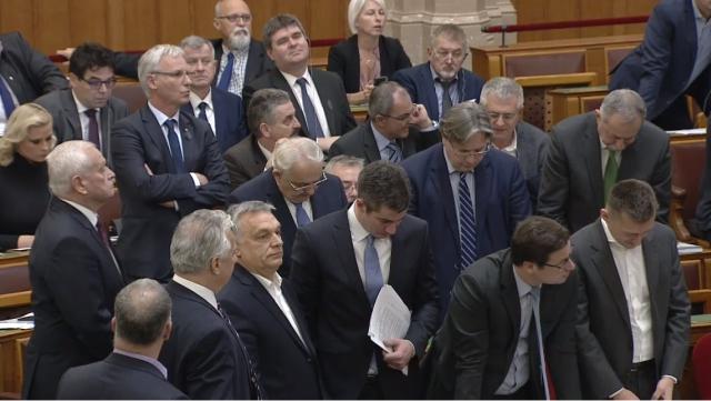 Latorcai János a padsorból vezeti az ülést (középen). Előtte sorfalat állnak a fideszes képviselők: Kósa Lajos, Semjén Zsolt, Kicsis Máté,  Gulyás Gergely és Rogán Antal.