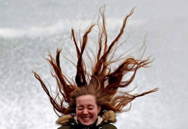 A woman reacts as her hair blows in the air on windy day in San Sebastian, in the Basque Country, northern Spain, 31 January 2019. The Basque Department of Security has issued an orange-level alert due to bad sea with waves reaching up to 6 meters high. EPA/Juan Herrero EPA/Juan Herrero