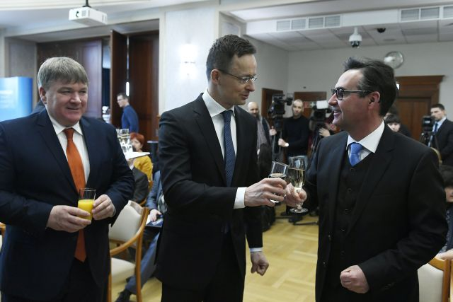 Szijjártó Péter külgazdasági és külügyminiszter (k) és Wolfgang Bochtler, a Mektec Europe GmbH. vezérigazgatója koccint, balról Szűcs Lajos, a térség fideszes országgyűlési képviselője a japán tulajdonú Enmech Hungary Kft. beruházását bejelentő  sajtótájékoztatón a Külgazdasági és Külügyminisztériumban 2019. február 15-én. Az autóipari alkatrészgyártó cég 6,4 milliárd forint értékben bővíti péceli üzemét, a legalább 250 új munkahelyet teremtő beruházást a kormány 641 millió forint vissza nem térítendő támogatással segíti. MTI/Koszticsák Szilárd