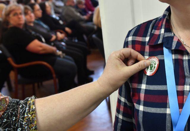 Matricát helyez egy dolgozó munkatársa ruhájára a Magyar Köztisztviselők, Közalkalmazottak és Közszolgálati Dolgozók Szakszervezete (MKKSZ) egynapos sztrájkjának elindításán tartott gyűlésen a XV. kerületi polgármesteri hivatalban (MTI/Máthé Zoltán)