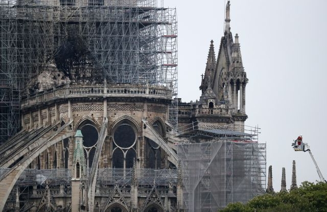 A firefighter stands in an aerial lift near the burnt roof after a massive fire destroyed the roof of the Notre-Dame Cathedral in Paris, France, 16 April 2019. A fire started in the late afternoon on 15 April in one of the most visited monuments of the French capital. EPA/IAN LANGSDON