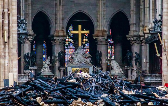 A view of the cross and the sculpture 'Pieta' by Nicholas Coustou behind debris inside the Notre-Dame de Paris in the aftermath of a fire that devastated the cathedral, in Paris, France, 16 April 2019. The fire started in the late afternoon on 15 April in one of the most visited monuments of the French capital. EPA/CHRISTOPHE PETIT TESSON