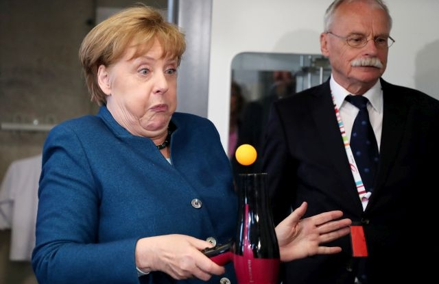 German Chancellor Angela Merkel experiments with a hair dryer and a tennis ball as she visits the youth university in Wuppertal, Germany, 13 May 2019. EPA/FRIEDEMANN VOGEL
