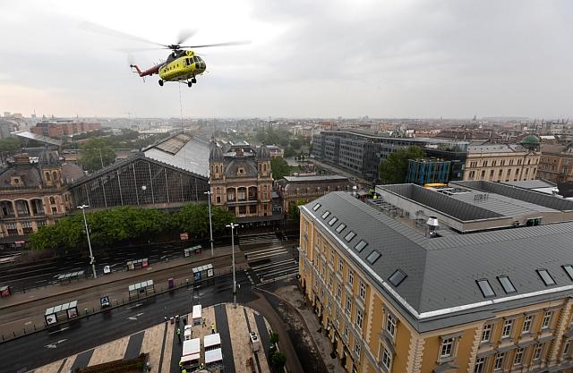 Dolgozók irányítanak gépészeti berendezéseket, amelyeket helikopter emel egy irodaház tetejére a Nyugati téren 2019. május 19-én. A művelet idejére lezárták a Teréz körút Podmaniczky utca és a Bajcsy-Zsilinszky út közötti szakaszát. MTI/Mohai Balázs