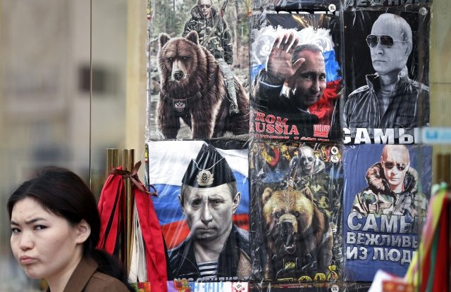 A Woman walks near a shop window with T-shirts featuring portraits of Russian President Vladimir Putin in the center of Moscow, Russia, 23 May 2019. EPA/YURI KOCHETKOV