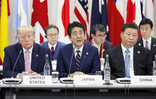 Japanese Prime Mnister Shinzo Abe delivers an opening speech next to US President Donald J. Trump (L) and Chinese President Xi Jinping (R) during a side-event on digital economy on the first day of the G20 summit in Osaka, western Japan, 28 June 2019. It is the first time Japan will host a G20 summit. The summit gathers leaders from 19 countries and the European Union to discuss topics such as global economy, trade and investment, innovation and employment. EPA/JAPAN POOL