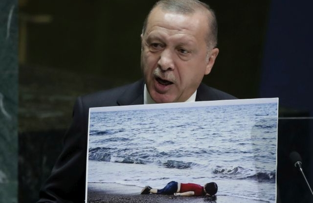 Turkish President Recep Tayyip Erdogan, holds a photograph showing the body of Alan Kurdi, the three-year-old Syrian boy who drowned in September 2015 while crossing the Mediterranean sea with his refugee family, as he addresses the general debate of the 74th session of the General Assembly of the United Nations at United Nations Headquarters in New York, New York, USA, 24 September 2019. The annual meeting of world leaders at the United Nations runs until 30 September 2019. EPA/JASON SZENES