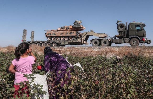 Seasonal workers cut a cotton while Turkish military vehicles carrying tanks as they are on the way to Northern Syria for a military operation in Kurdish areas, near the Syrian border, near Akcakale district in Sanliurfa, Turkey 12 October 2019. Turkey has launched an offensive targeting Kurdish forces in north-eastern Syria, days after the US withdrew troops from the area. EPA/SEDAT SUNA