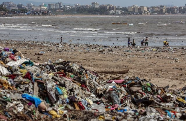4 Indian people look for reusable things amidst left over eatables and plastic waste, near the Arabian Sea coast at Versova beach in Mumbai, India, 27 September 2019. Millions of people across the world are taking part in demonstrations demanding action on climate issues. The Global Climate Strike Week is held from 20 September to 27 September 2019. EPA/DIVYAKANT SOLANKI
