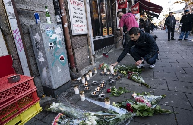A man places flowers in tribute to victims of a shooting while a restaurant employee sweeps broken glass at the crime scene in Malmo, Sweden, 10 November 2019. A 15-year-old was fatally hit and another severely wounded when attackers opened fire on a pizzeria before fleeing the scene on bicycles in Malmolate 09 November 2019. EPA/JOHAN NILSSON SWEDEN OUT
