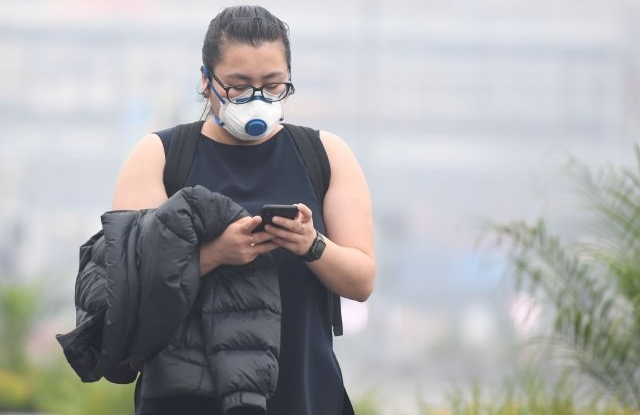 A pedestrian wears a face mask amid smoke haze from bushfires in Melbourne, Australia, 14 January 2020. Smoke haze from the East Gippsland bushfires has drifted across Victoria reaching Melbourne prompting health warnings. EPA/ERIK ANDERSON