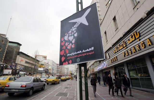 People walk past a poster reading in Persian 'we are all in pain and sympathize' to honor the victims of Ukrainian passenger jet accidentally shot down last week, in a street of Tehran, Iran, 13 January 2020. Media reported Iran admitted that Ukraine International Airlines flight PS752 was shot down due to human error. EPA/ABEDIN TAHERKENAREH