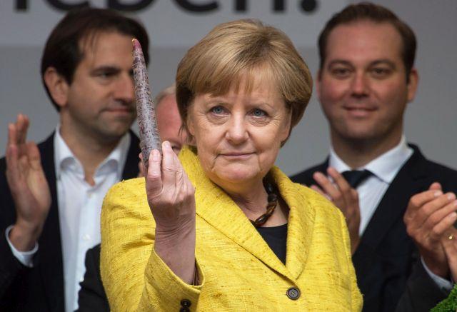 Angela Merkel német kancellár, a Kereszténydemokrata Unió (CDU) elnöke egy fekete répát mutat fel egy választási kampányeseményen a dél-németországi Freiburg im Breisgauban 2017. szeptember 18-án. De mi lehet az üzenet? Forrás: MTI/EPA/Daniel Kopatsch