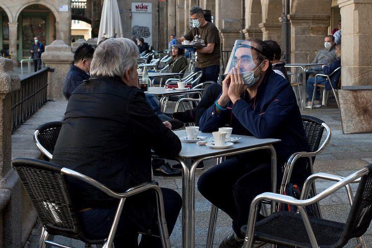 Beszélgető emberek egy újranyitott bár teraszán a galíciai Ourensében Északnyugat-Spanyolországban 2020. május 11-én. EPA/Brais Lorenzo