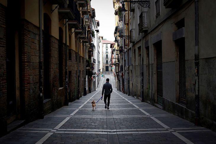 Egy férfi sétáltatja a kutyáját egy üres utcán Pamplonában (Baszkföld, Spanyolország) 2020. március 28-án. EPA/VILLAR LOPEZ