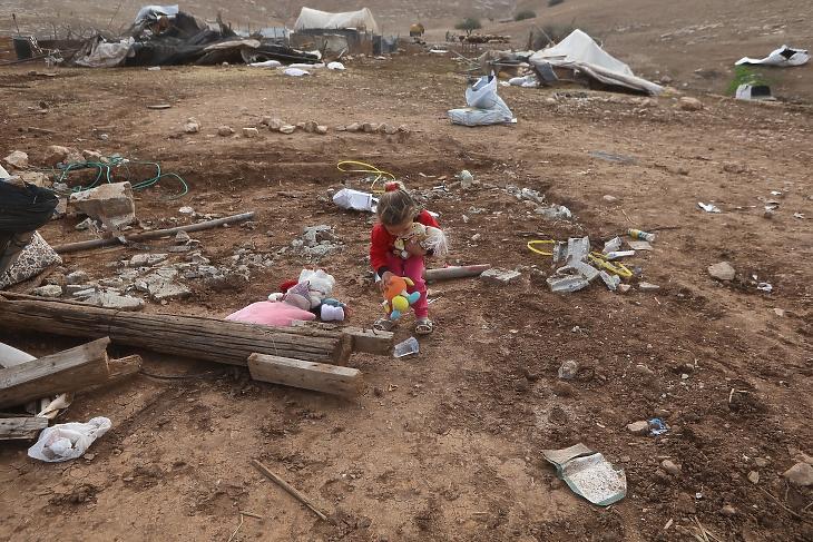 Egy palesztin gyerek szedi össze a játékait egy, az izraeli hadsereg által megsemmisített település romjai között 2020. november 6-án. Fotó: EPA/Alaa Badarneh