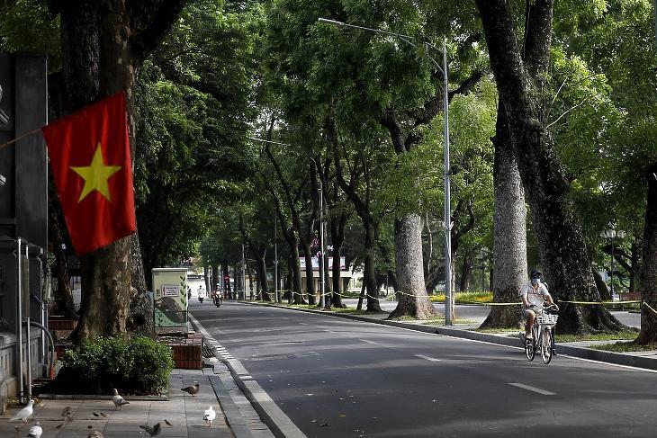 Egy férfi kerékpározik Hanoi utcáin 2021. július 24-én. A várost mától 15 napra zárják le, hogy fékezzék a koronavírus terjedését, Ho Si Minh-városban pedig augusztus 1-jéig terjesztik ki a lezárást. Fotó: EPA / Luong Thai Linh