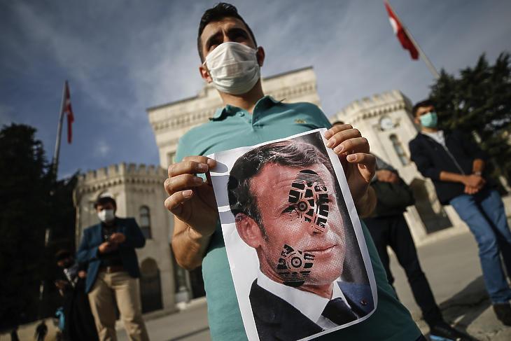 Emmanuel Macron francia elnök fényképét tartja kezében egy férfi, amelyen egy cipőtalp lenyomata látható egy tüntetésen Isztambulban 2020. október 25-én. Recep Tayyip Erdogan török elnök előző nap azt kifogásolta, hogy Macron azt mondta, hogy megvédi Franciaország szekuláris értékrendjét, és erőteljesebb fellépést helyezett kilátásbaa radikális iszlámmal szemben Samuel Paty tanár brutális meggyilkolását követően. (Fotó: MTI/AP/Emrah Gürel)