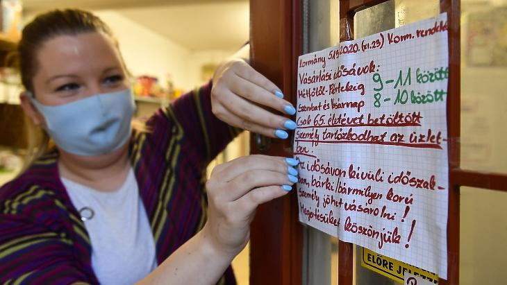 Vásárlási idősávról tájékoztató feliratot ragaszt ki egy eladó egy élelmiszerüzlet ajtajára Debrecenben 2020. november 24-én. Fotó: MTI/Czeglédi Zsolt