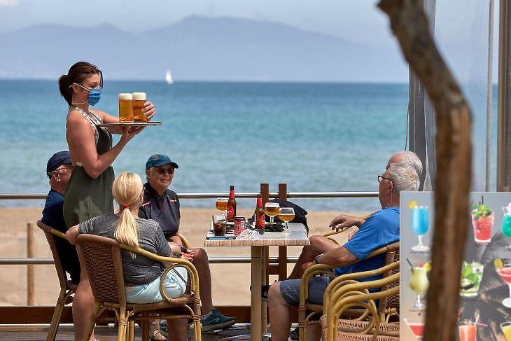 Védőmaszkot viselő pincérnő szolgálja ki a vendégeket egy bár teraszán a katalóniai  L'Escalában 2020. május 28-án. EPA/David Borrat