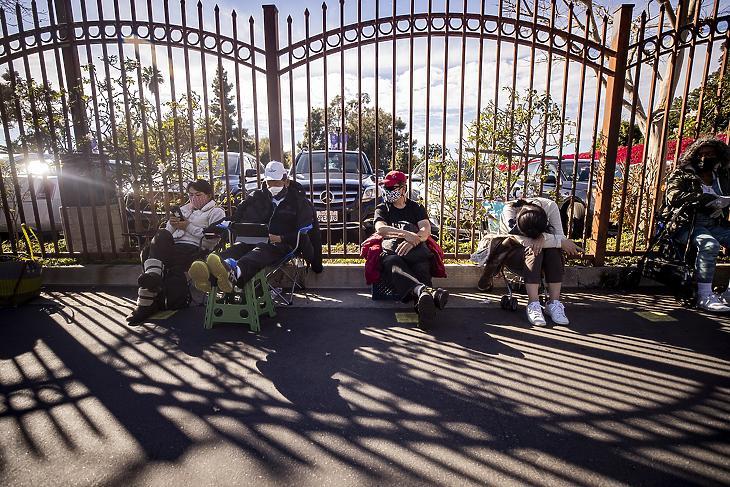 A megmaradt koronavírus elleni vakcinára várakozó, vakcinavadászoknak nevezett emberek egy kerítés mellett ülnek a kaliforniai Los Angeles egyik kórházában működő oltópont közelében 2021. február 2-án. (Fotó: MTI/EPA/Etienne Laurent)