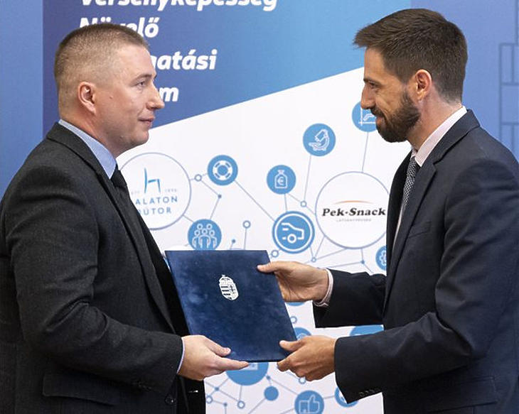 Kalauz Károly, a Balaton Bútor Kft. ügyvezetője (b) átveszi a versenyképességi program támogató okiratát Magyar Leventétől, a Külgazdasági és Külügyminisztérium parlamenti államtitkárától a Külgazdasági és Külügyminisztériumban 2020. május 21-én.  (Fotó: MTI /Szigetváry Zsolt)