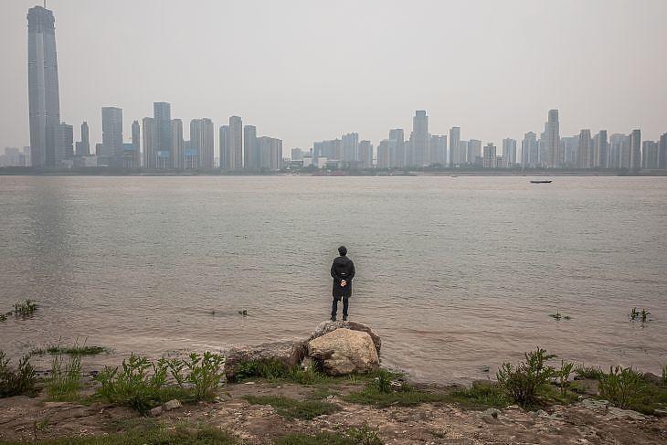 Egy férfi áll a Jangce-folyó partján Vuhanban 2020. április 3-án. EPA/ROMAN PILIPEY