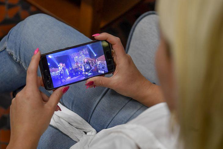 Egy lány a telefonján nézi a Tankcsapda zenekar online közvetítésű koncertjét 2020. március 20-án. MTI/Czeglédi Zsolt
