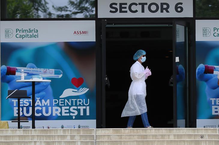Egy román egészségügyi dolgozó a bukaresti nemzeti stadion előtt júniusban. A stadiont teszt-központtá alakították. Fotó: EPA / Robert Ghement.