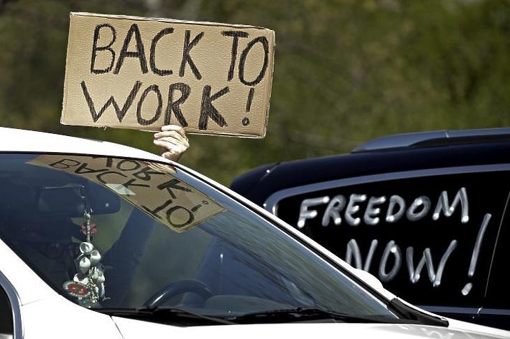 Vissza a munkába! feliratú plakátot tart a kezében egy autóban ülő tüntető a koronavírus-járvány miatt bevezetett korlátozó intézkedések elleni tüntetésen Kansas állam parlamentje előtt 2020. április 23-án. (Fotó: MTI/AP/Charlie Riedel)