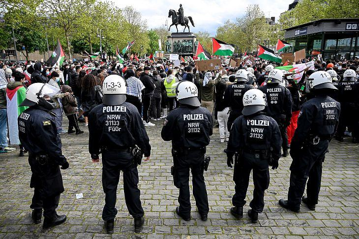 A Nakba-nap, azaz a katasztrófa nap elnevezésű palesztin gyásznap alkalmából tartott felvonulás résztvevői a németországi Kölnben - és a felvonulást biztosító rendőrök 2021. május 14-én. A Közel-Keleten kíújult konfliktus miatt országszerte tartottak tüntetéseket a palesztinok mellett és az antiszemitizmus ellen is. Fotó: Sascha Steinbach / EPA