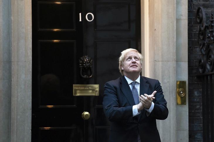A koronavírus okozta betegségből felgyógyult Boris Johnson brit miniszterelnök a londoni kormányfői rezidencia, a Downing Street 10. kapujában 2020. április 30-án részt vesz a tapsoljunk a rólunk gondoskodóknak mottóval meghirdetett hetenkénti akcióban, amikor az emberek Nagy-Britannia-szerte tapssal köszönik meg mindazok tevékenységét, akik a koronavírus-járvány alatt a lakosság biztonságáért, egészségéért, ellátásáért, az ország működőképességének fenntartásáért dolgoznak. MTI/EPA/Will Oliver