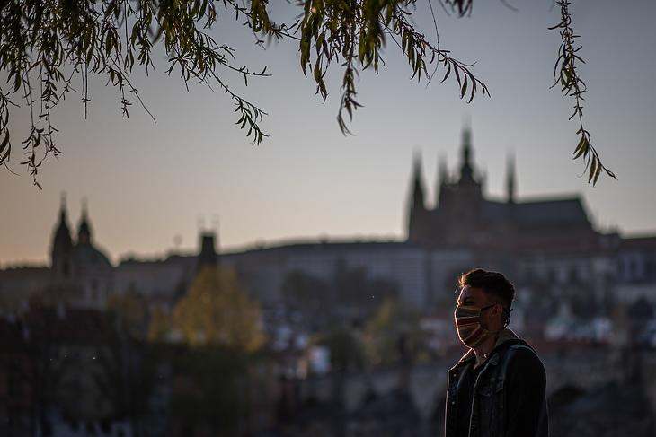 Egy védőmaszkos férfi áll a Moldva partján 2020. április 23-án. A háttérben a Prágai Vár. EPA/MARTIN DIVISEK