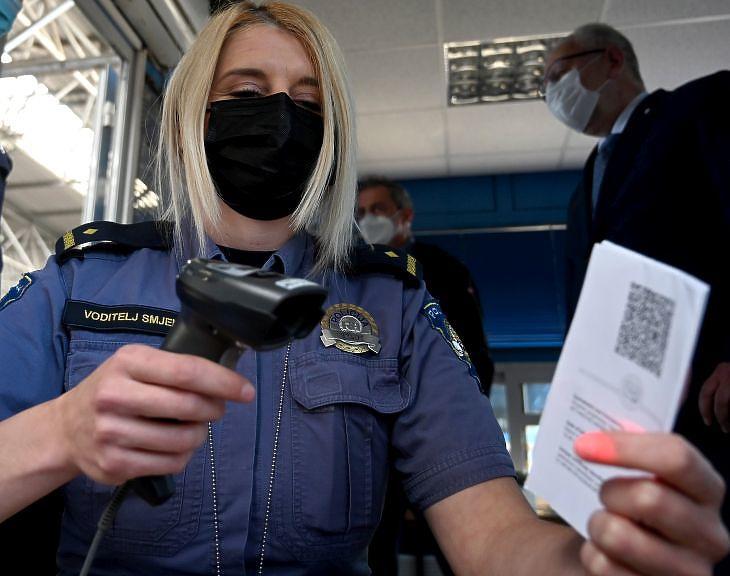 Az Európai Unió digitális Covid-igazolását ellenőrzi egy horvát határőr a Horvátország és Szlovénia közötti Bregana határállomáson 2021. június 2-án. Magyarországról beutazva viszont már csak egy személyi kell. MTI/EPA/Antonio Bat