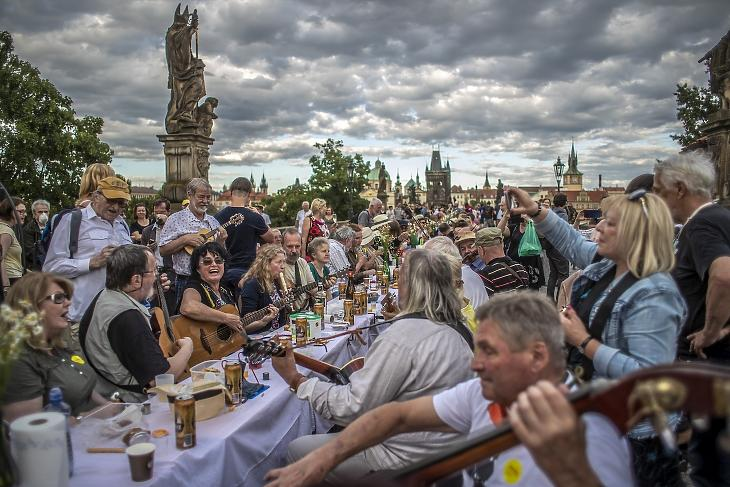 Zenészek játszanak az 515 méter hosszú asztalnál helyet foglaló vendégeknek a prágai Károly hídon 2020. június 30-án. A nagyszabású vacsorával a koronavírus-járvány miatt elrendelt korlátozások feloldását ünnepelték a szervezők és a résztvevők. MTI/EPA/Martin Divisek