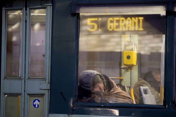 Hajléktalan alszik egy buszon Rómában 2020. március 27-én. EPA/MASSIMO PERCOSSI