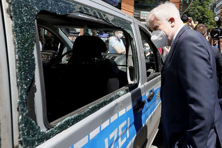Horst Seehofer német belügyminiszter egy szombat éjjel megrongált rendőrautót tekint meg Stuttgartban 2020. június 22-én. EPA/RONALD WITTEK