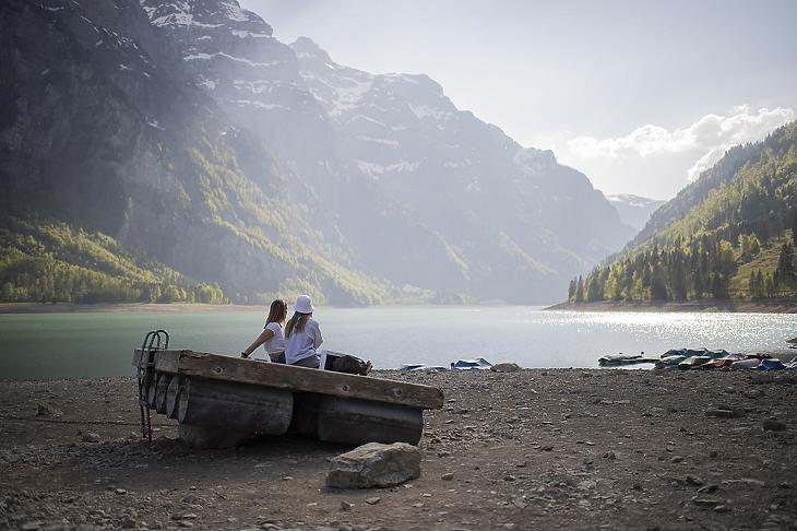 Az alacsony vízszintű Klöntal-tó partján ül két nő a svájci Glarusban 2020. április 23-án. MTI/EPA/Keystone/Gian Ehrenzeller