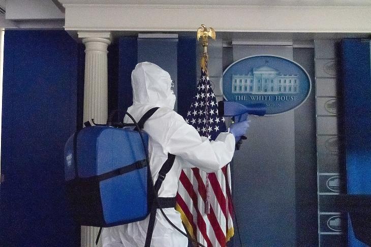 A koronavírus-járvány miatt védőöltözetet viselő dolgozó fertőtleníti a washingtoni Fehér Házban (Fotó: MTI/AP/Alex Brandon)