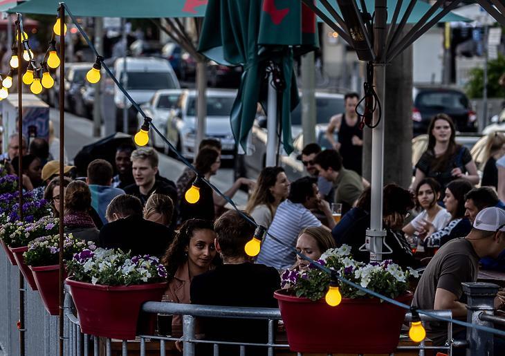 Egy berlini étterem kültéren fogyasztó vendégei, 2021. június 4-én. Teraszozni már lehet maszk nélkül. (Fotó: MTI/EPA/Filip Singer)